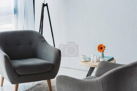 Cozy office in light tones with grey chairs and table