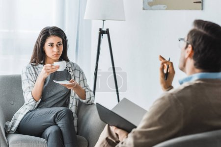 Woman drinking coffee and listening to male doctor recommendations