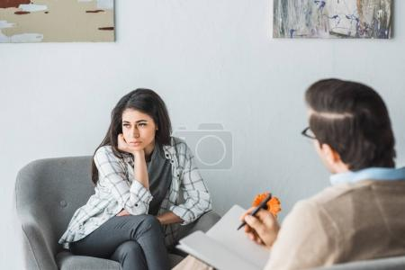 Young woman visiting psychotherapist in cozy doctor office