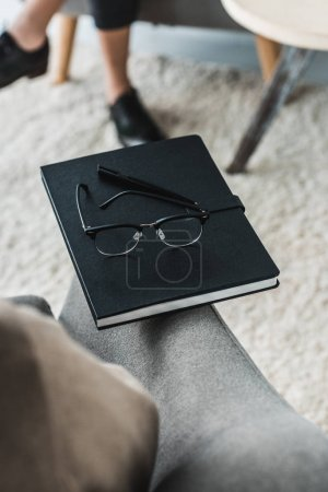 Close-up view of glasses on notebook in front of woman in doctor office