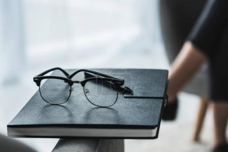 Close-up view of glasses on notebook in front of female patient