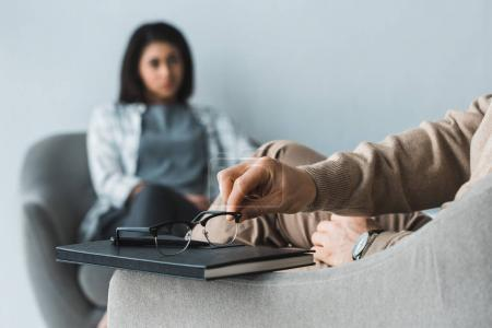Close-up view of therapist putting glasses in front of female patient