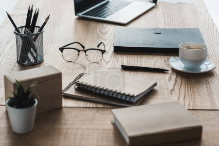 Photo for Business office workplace with laptop and notepads on table - Royalty Free Image