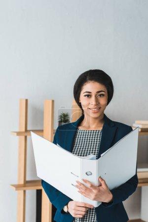 Photo pour Femme souriante tenant dossier de bureau moderne - image libre de droit