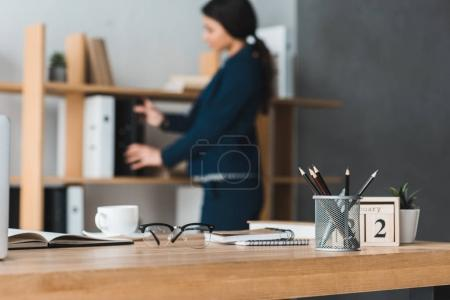 Office table in front of businesswoman stacking folders
