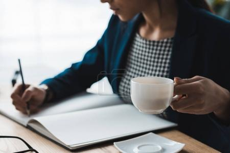 Photo for Close-up view of businesswoman drinking coffee in office - Royalty Free Image