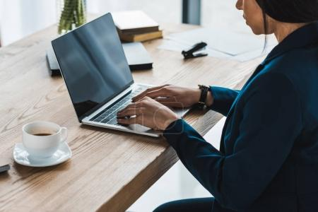 African american businesswoman typing on laptop by table in office