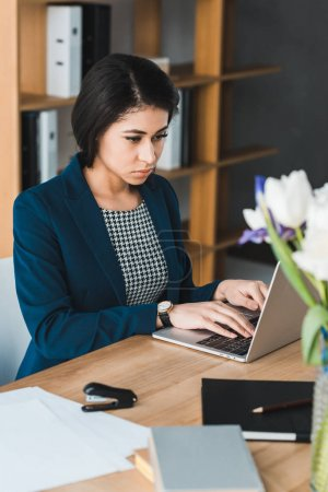 Photo for Attractive businesswoman looking at laptop screen by office table - Royalty Free Image