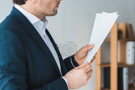 Photo pour Vue rapprochée d'homme d'affaires, étudier des documents au bureau - image libre de droit