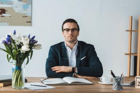 Serious businessman sitting straight by working table