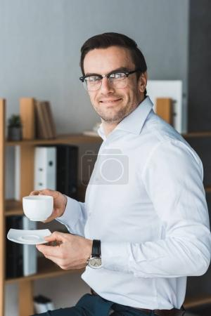Smiling male manager enjoying coffee during break in modern office