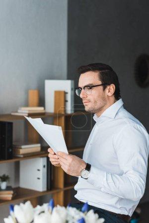 Foto de Empresario reflexivo estudio de papeles en la oficina moderna - Imagen libre de derechos