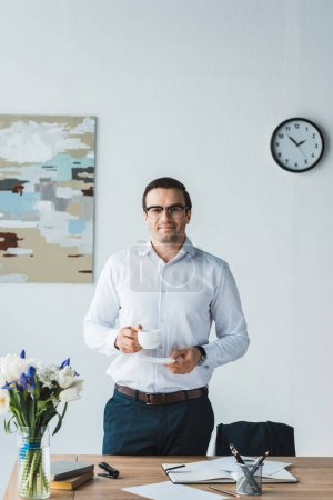 Photo for Smiling businessman wearing glasses holding coffee cup in modern office - Royalty Free Image