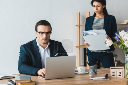 Businesswoman with folders standing by male colleagues working on laptop