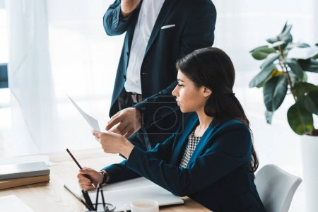 Photo for Businesswoman showing documents to her male colleague in office - Royalty Free Image
