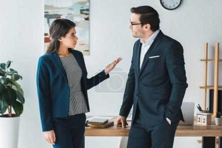 Businessman and businesswoman having a discussion about project in modern office