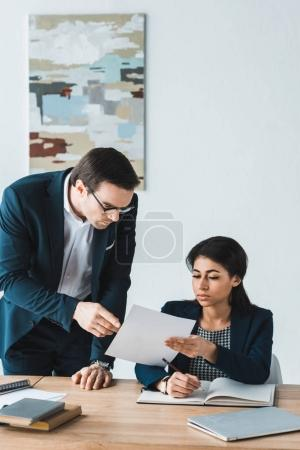 Businesswoman showing contract papers to her male colleague in office
