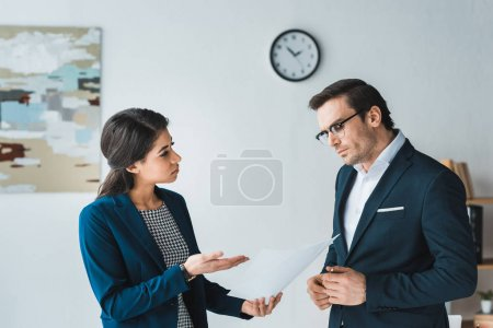 Colleagues in business suits arguing about contract details in modern office