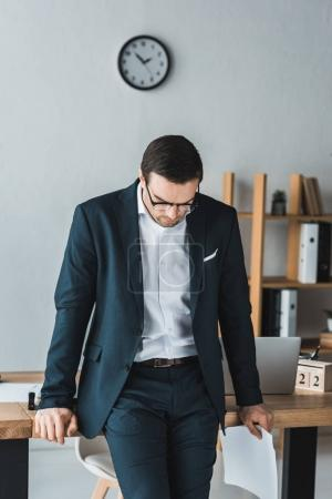 Thoughtful businessman wearing suit and glasses standing by table in office