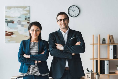 Businessman and businesswoman smiling and standing in modern office