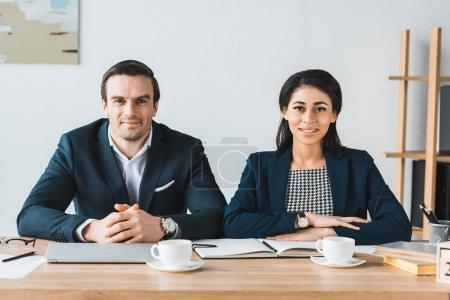Smiling businessman and businesswoman working by table with coffee cups in light office