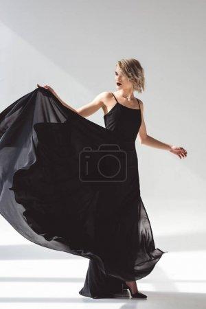 Photo pour Belle jeune fille en robe noire élégante, sur fond gris - image libre de droit