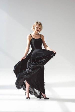 Photo pour Belle fille élégante posant dans une robe noire élégante, sur fond gris - image libre de droit