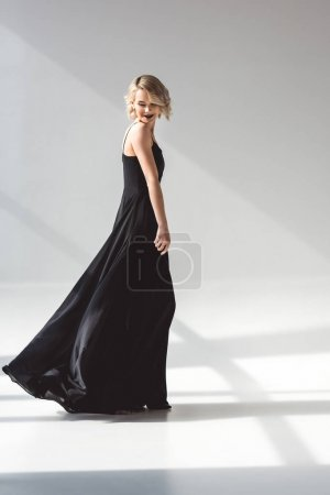 fashionable young woman posing in elegant black dress, on grey