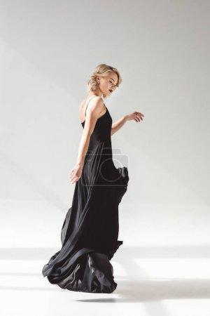 Photo pour Femme élégante qui pose en robe noire élégante pour Shooting de mode, sur fond gris - image libre de droit