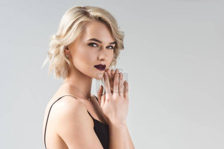 Photo for Blonde young woman posing in elegant black dress, isolated on grey - Royalty Free Image