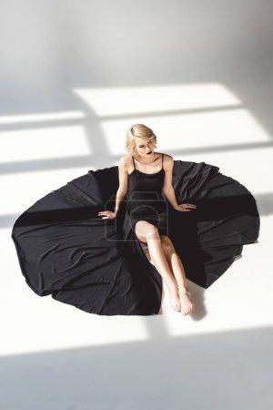Photo pour Jolie fille à la mode, posant dans une robe noire élégante, sur fond gris - image libre de droit