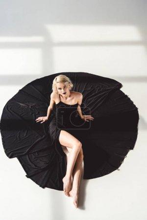 beautiful blonde girl posing in elegant black dress, on grey