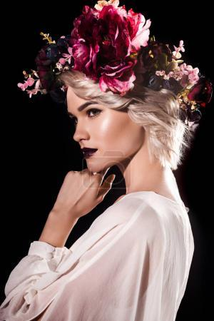 attractive blonde girl with makeup posing in floral wreath, isolated on black