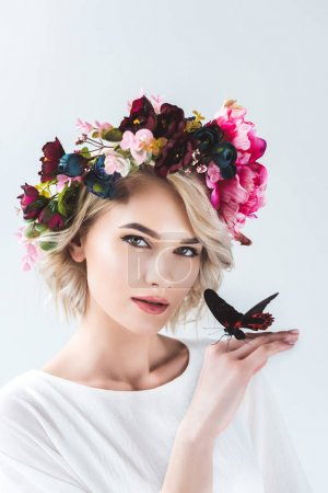 attractive girl posing in flower wreath with beautiful butterfly on hand, isolated on grey