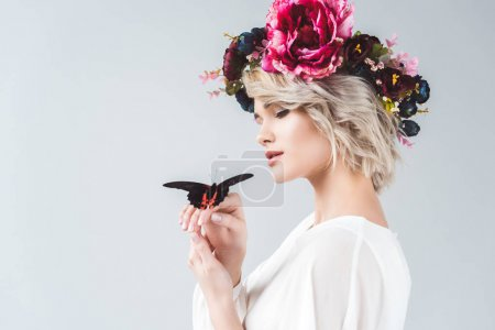 beautiful girl posing in floral wreath with alive butterfly on hands, isolated on grey