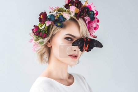 beautiful young woman posing in floral wreath with butterfly, isolated on grey