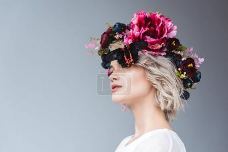 fashionable girl posing in floral wreath with butterfly, isolated on grey