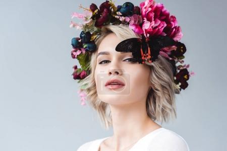 Photo pour Belle fille posant en couronne florale avec papillon, isolé sur gris - image libre de droit