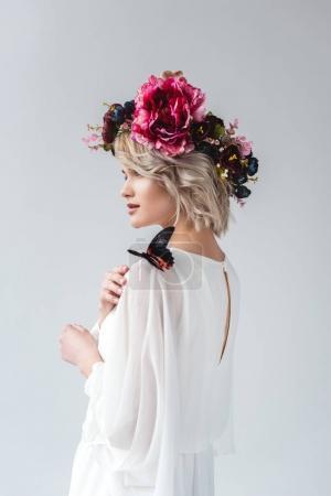 Photo pour Belle fille posant en couronne de fleurs avec papillon sur l'épaule, isolé sur gris - image libre de droit