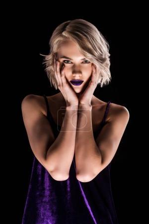 Foto de Atractiva chica rubia posando en vestido púrpura, aislado en negro - Imagen libre de derechos