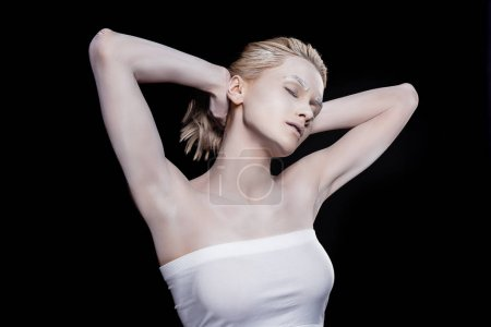 young woman with closed eyes posing with white makeup, isolated on black