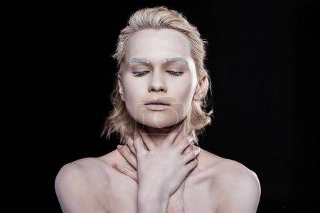 Photo pour Jeune femme tendre posant avec du maquillage blanc, isolé sur noir - image libre de droit