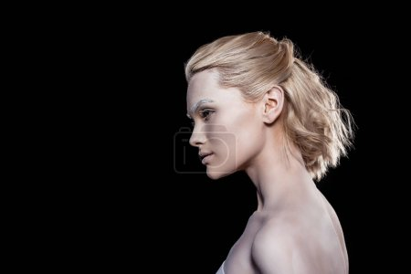 young blonde woman posing with white makeup, isolated on black