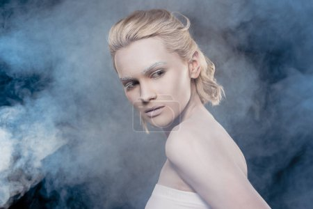 beautiful blonde girl with white makeup posing for fashion shoot in smoky studio