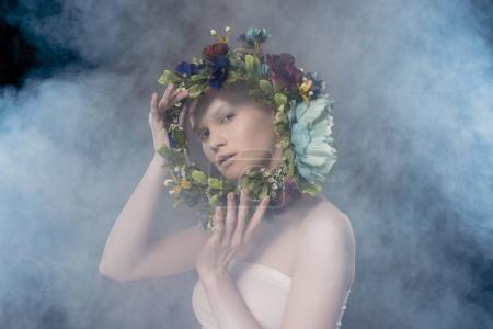 Photo pour Jolie fille tendre avec le maquillage blanc tenant la Couronne florale dans studio fumé - image libre de droit