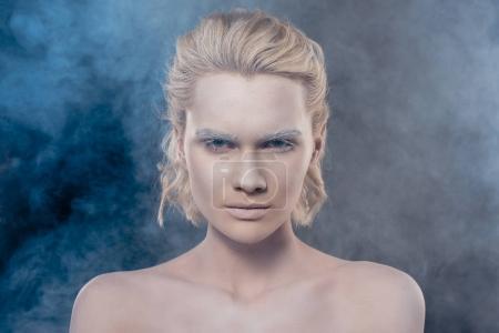 Photo pour Portrait de jeune fille blonde à la mode avec le maquillage blanc en studio fumé - image libre de droit