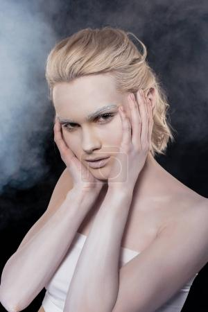 portrait of beautiful blonde girl with white makeup in smoky studio
