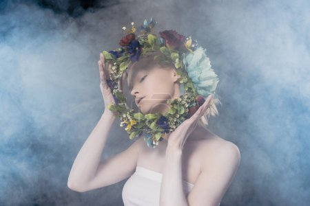 tender girl with white makeup holding floral wreath in smoky studio