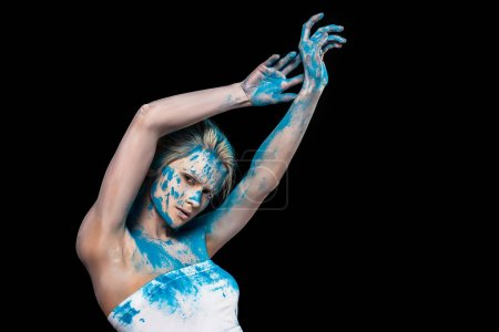 young woman posing in blue powder powder, isolated on black