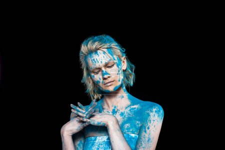 young woman with closed eyes in blue powder powder, isolated on black